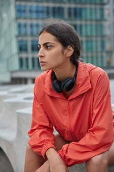 Woman listens audio podcast during training break sits outside feels tired poses in urban street thinks about new goals achievements wears sports outfit rests after physical practice