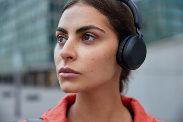 Woman listens audio track in wireless headphones daydreaming while walking outdoors thinks about new sport achievements poses against blurred