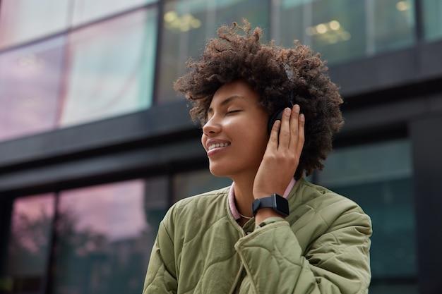 女性は目を閉じてオーディオトラックを聴きますヘッドフォンでお気に入りの音楽を楽しんでいますストリートウェアで自由な時間を過ごしますスマートウォッチはポジティブなポッドキャストのお気に入りの曲が好きです