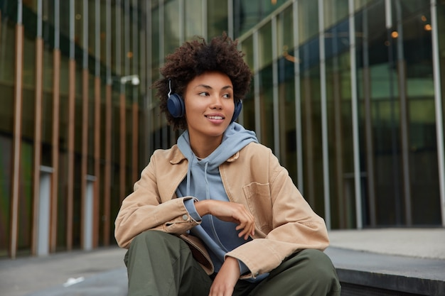 Woman listens favorite music playlist thinks about audio information ponders on song text dressed in fashionable clothes enjoys leisure time