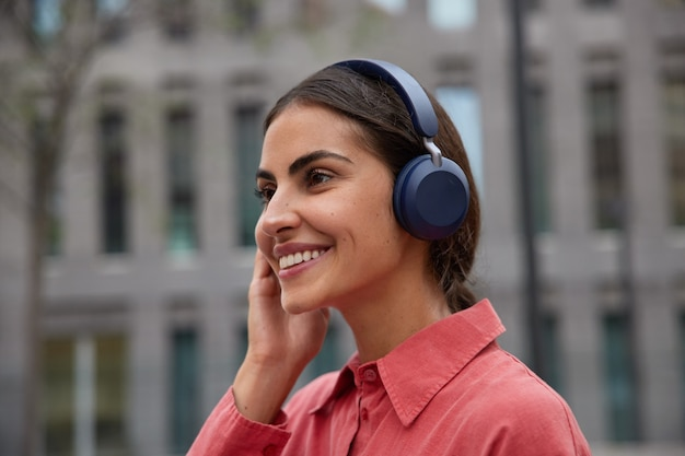Woman listens music in headphones outdoors smiles gently focused forward enjoys favorite song wears red shirt poses against blurred