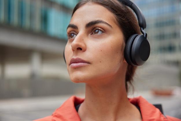 女性は、毎日の練習が青ざめたものに対して歩いた後、屋外でのトレーニングの休憩中にプレイリストのお気に入りの音楽を聴きます