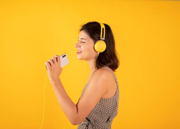 女性はヘッドフォンで音楽を聴きます
