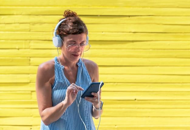女性はヘッドフォンとスマートフォンで音楽を聴きます