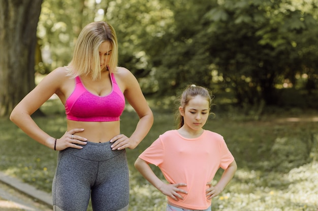 Woman and little girl do excercises outside