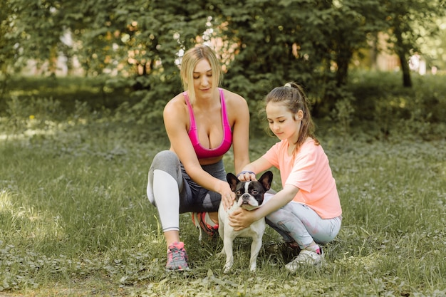 Woman and little girl go walking with their dog in the park