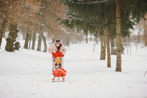 Donna e bambina in un parco con la slitta