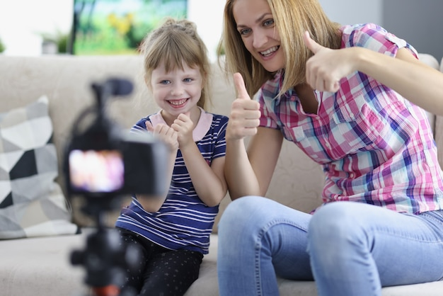 Woman and little girl showing thumb up in front of camera at home