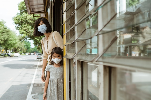 A woman and little girl wearing a mask stands waiting for the bus at the bus stop
