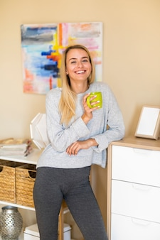 Woman in the living room smiles and holding a mug