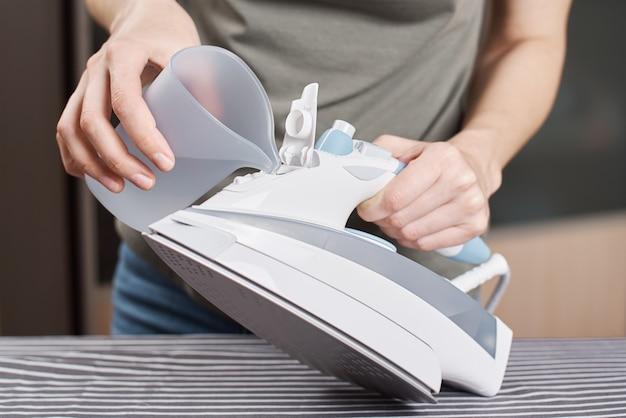 女性は鉄に水を入れます。アイロンがけのためにアイロンを準備する