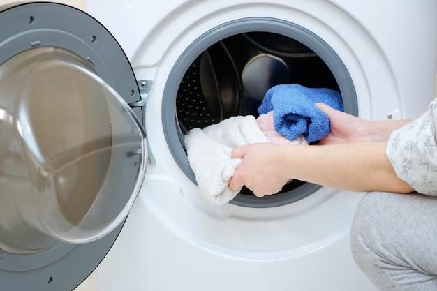 開いたドアのクローズビューで白いケースのモダンな洗濯機に汚れたタオルをロードする女性 Premium写真
