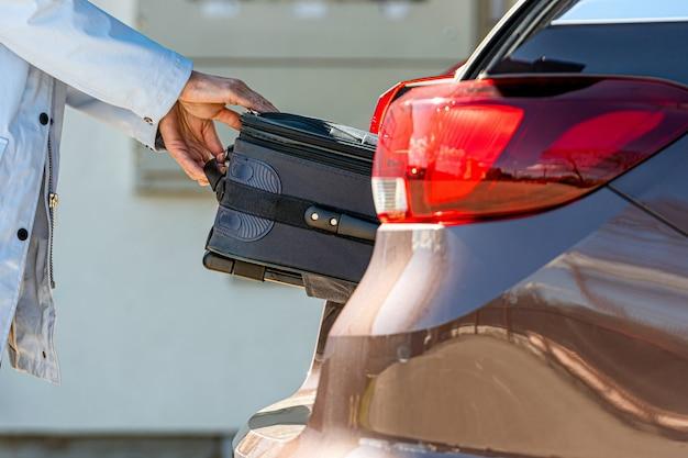 Женщина загружает чемодан в багажник автомобиля, подготовка к поездке