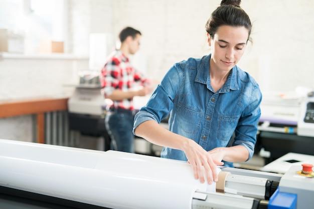 Woman loading wide format printer