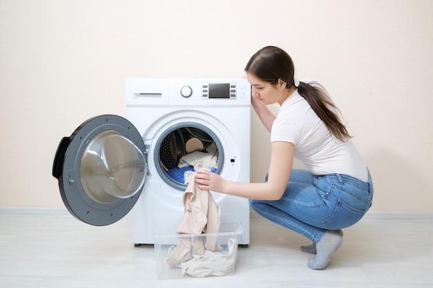 베이지색 벽 근처 세탁기에 더러운 옷을 싣는 여자