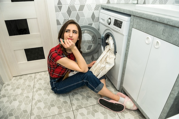 女性は洗濯機に洗濯物を入れます。