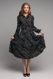 Woman in long black dress posing