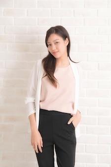 Женщина с длинными каштановыми волосами улыбается и смотрит на ее вид сбоку в черной футболке и джинсах, стоя positng на стене бежевого цвета.
