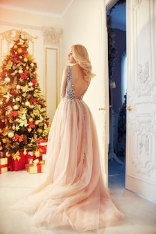 Woman in a long cream-coloured dress, standing near the christmas tree