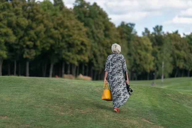 Woman in a long dress carrying a handbag and camera on a tripod walking over neatly cut grass on an embankment towards woodland trees in a rear view