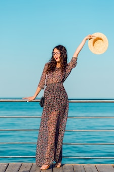 Woman in long dress and straw hat having fun by the sea