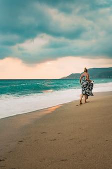 Woman in long dress walking on seashore