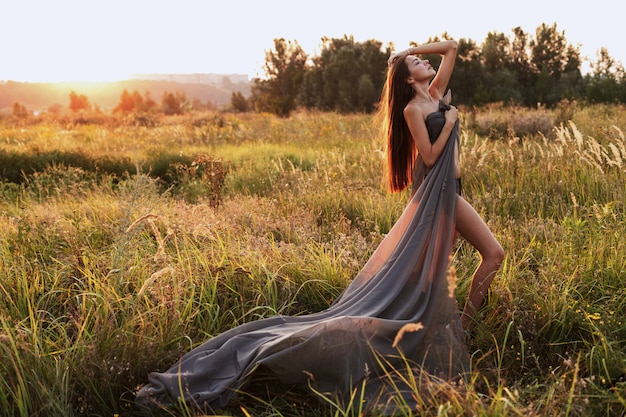 Woman in a long gray dress in a field at sunset