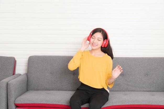 ソファでリラックスして赤いヘッドフォンで黄色いシャツを着ている女性の長い髪、彼女は音楽を聴いています、