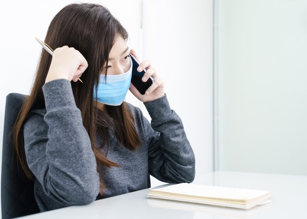 Woman long hair wearing protective mask holding and using mobile phone