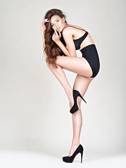 Gambe lunghe donna in tacchi alti con un corpo perfetto. la modella fahsion posa in studio indossando mutandine nere