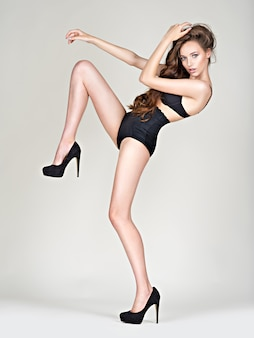 Woman long legs in high heels with perfect body. fahsion model poses at studio wering black panties