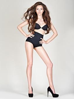 完璧なボディでハイヒールの女性の長い脚。ファションモデルがスタジオでポーズをとる黒いパンティー