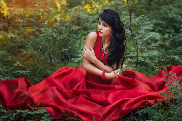 Woman in a long red dress alone in the forest