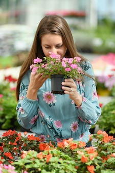 Woman in long sleeve shirt smelling pink flowers