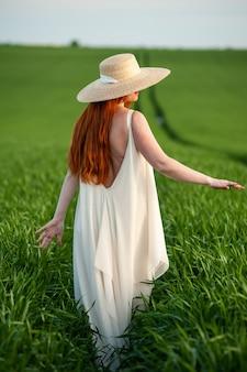 Woman in long white dress on a green field