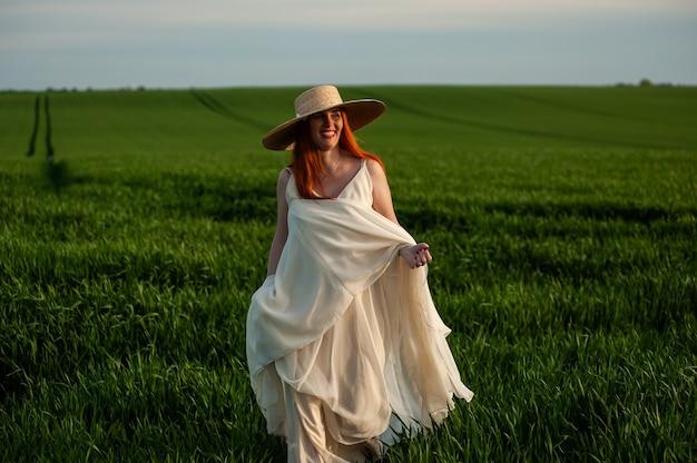 Woman in long white dress outdoor in green field