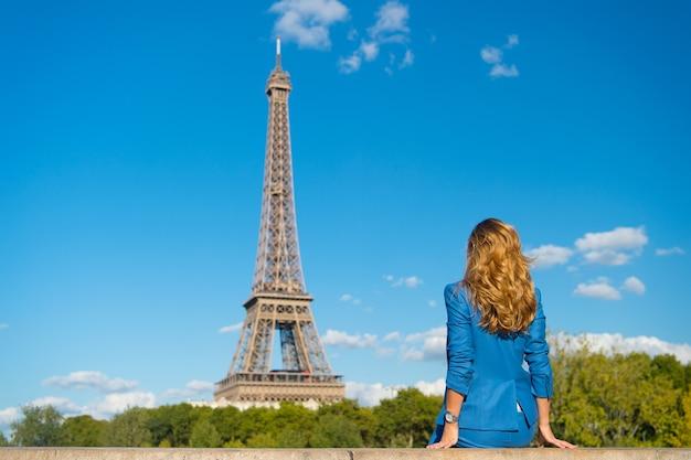 女性は、パリ、フランスのエッフェル塔を見てください。長い髪、髪型、背面図の青いドレスの女性。