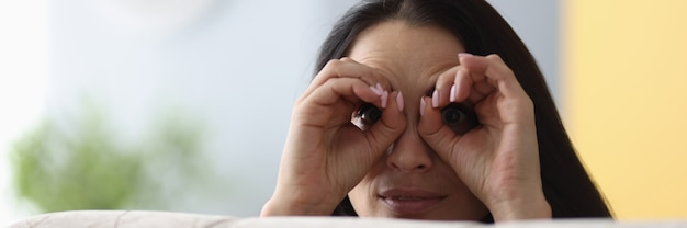 Woman look out from behind sofa and make binoculars with her hands.