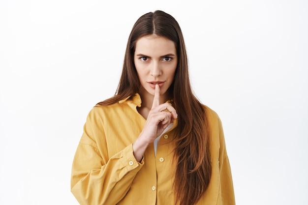 Женщина смотрит угрожающе и замолкает, говорит молчать, хранить в секрете, если только не делает табу и серьезно смотрит вперед, стоя над белой стеной.