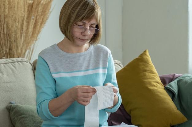 Женщина смотрит чек из супермаркета, отслеживая расходы и составляя бюджет