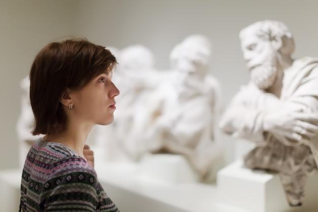 Женщина ищет старинные скульптуры