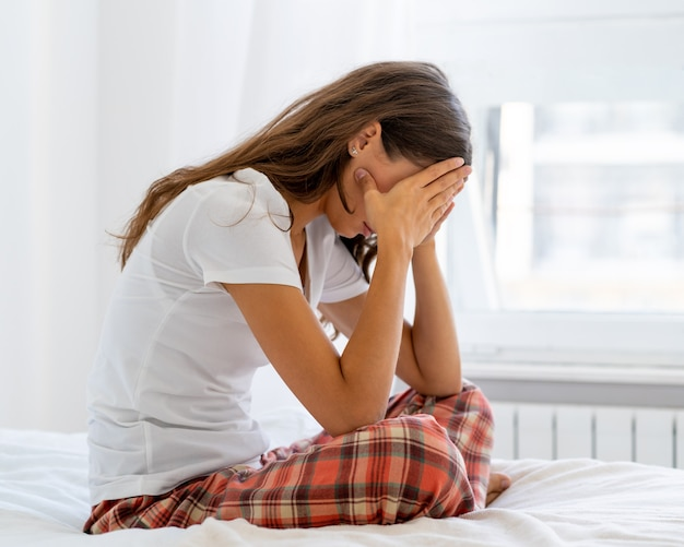 Женщина с тревогой смотрит в сторону, трогая рукой лоб и волосы.