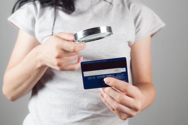 虫眼鏡で銀行カードを見ている女性