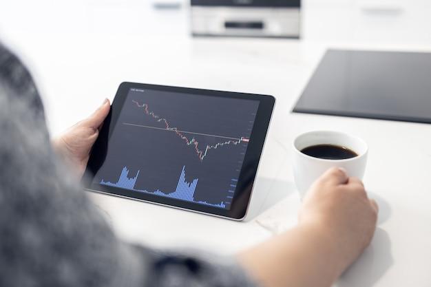 Женщина смотрит на цифровой планшет с диаграммой фондового рынка торговля дома концепции