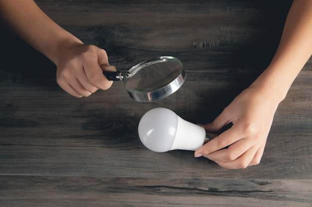 Женщина смотрит на лампочку с увеличительным стеклом