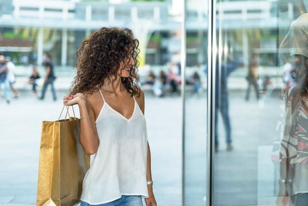 쇼핑하는 동안 상점 창을 보는 여자