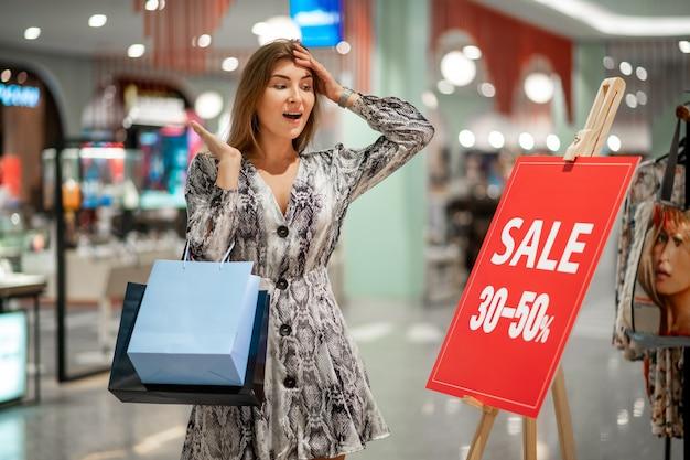 セールで看板を見ている女性