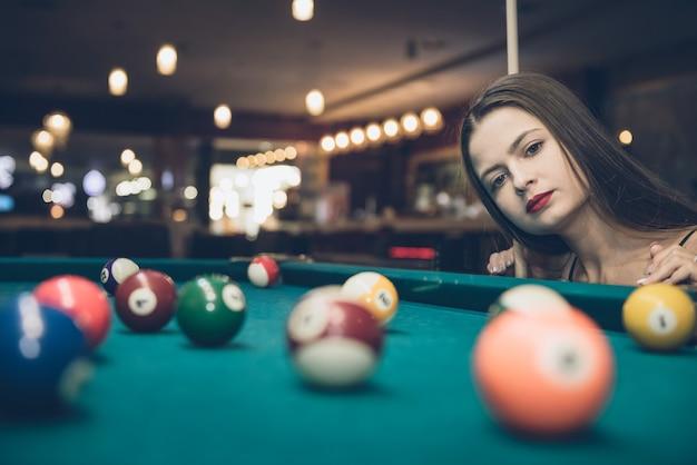 Женщина смотрит на бильярдный шар в пабе Premium Фотографии