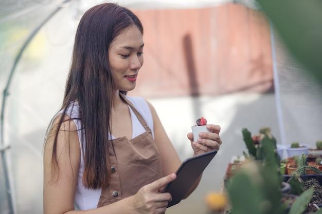 온실 정원 센터에서 선인장을 바라보는 여성, 작은 선인장을 바라보는 아시아 젊은 여성