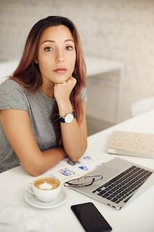 Женщина смотрит в камеру, используя ноутбук, пить кофе в кафе или коворкинге или в кампусе.